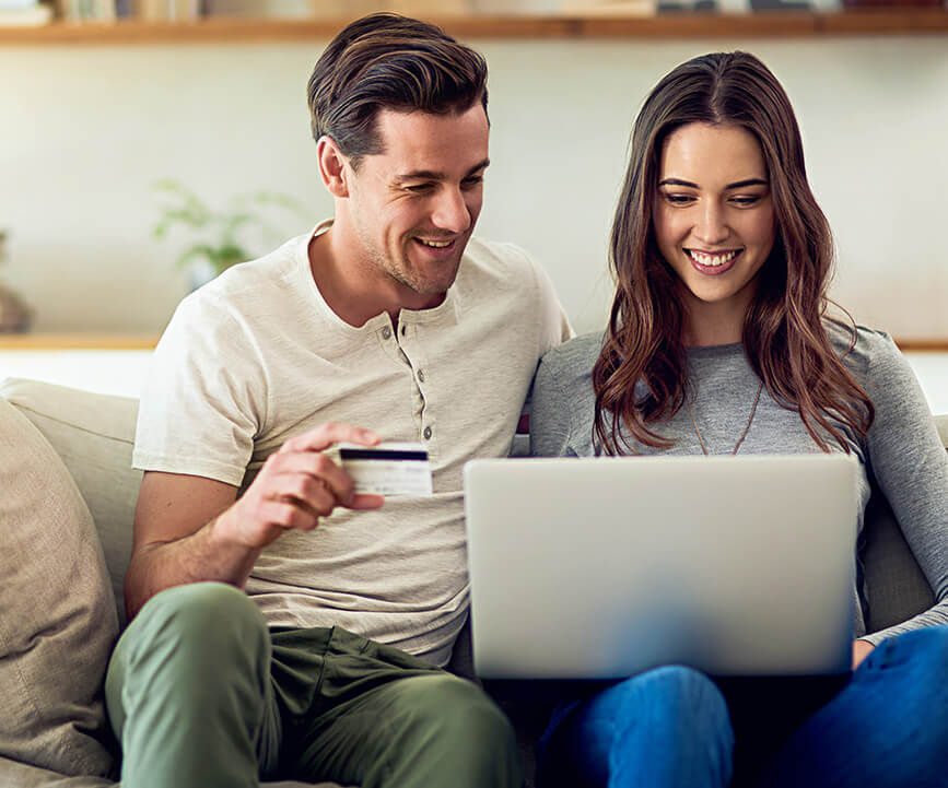 young couple sitting on the couch, paying a bill online together