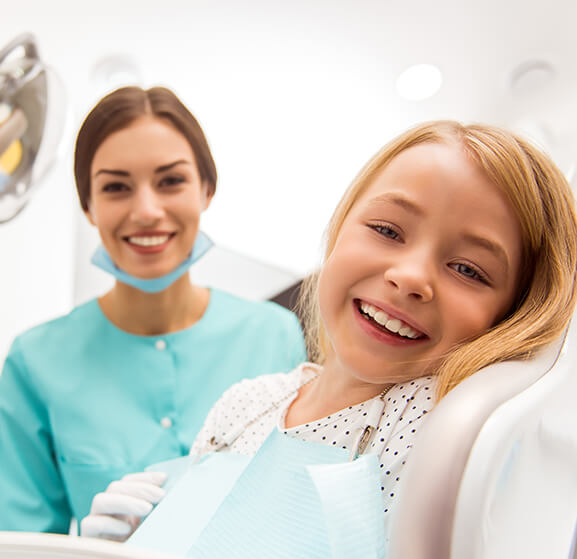 smiling girl sitting in a dental chair next to her dentist